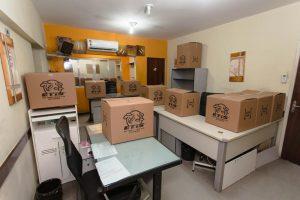Na imagem pode-se ver mesas com caixas com o emblema da ETIS preparadas para o transporte comercial